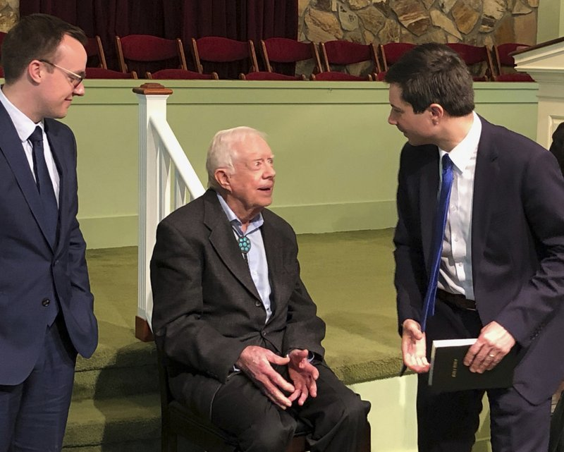 FILE - In this Sunday, May 5, 2019 file photo, Democratic presidential candidate Pete Buttigieg, right, and his husband, Chasten Glezman Buttigieg, left, speak with former President Jimmy Carter at Carter's Sunday school class in Plains, Ga. Carter has never been known as a key player in Democratic Party politics, but he's re-emerging in the 2020 is presidential race as some candidates go to Plains, Ga., to seek the 94-year-old's advice. (AP Photo/Paul Newberry, File)