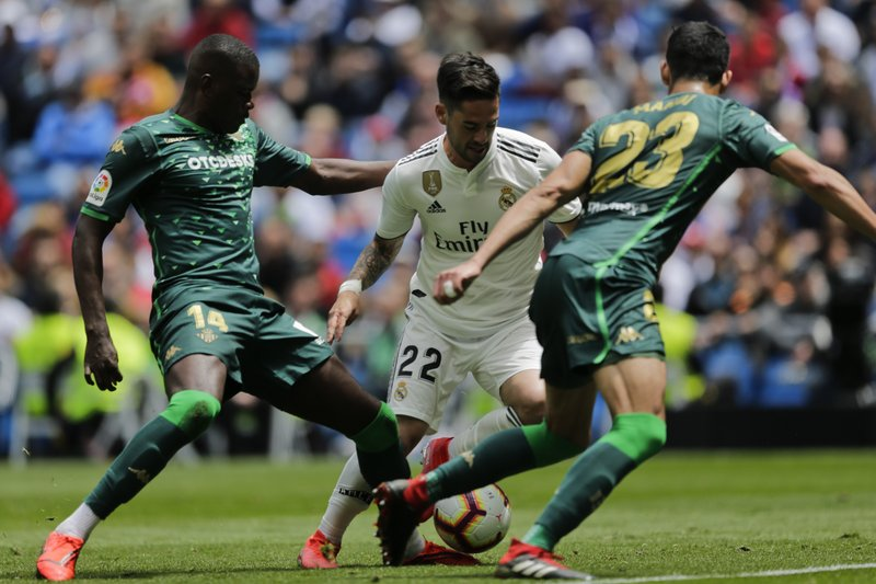 Real Madrid's Isco, center, duels for the ball against Betis player William Silva de Carvalho, left, and Betis player Aissa Mandi during a Spanish La Liga soccer match at the Santiago Bernabeu stadium in Madrid, Spain, Sunday, May 19, 2019. (AP Photo/Bernat Armangue)