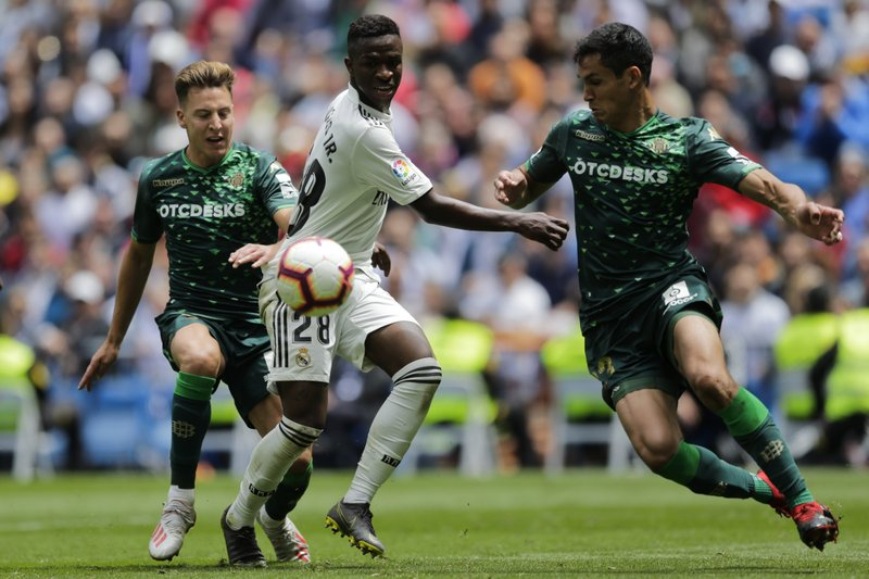 Real Madrid's Vinicius Junior, center, duels for the ball against Betis player Francis Guerrero, left, and Betis player Aissa Mandi during a Spanish La Liga soccer match at the Santiago Bernabeu stadium in Madrid, Spain, Sunday, May 19, 2019. (AP Photo/Bernat Armangue)