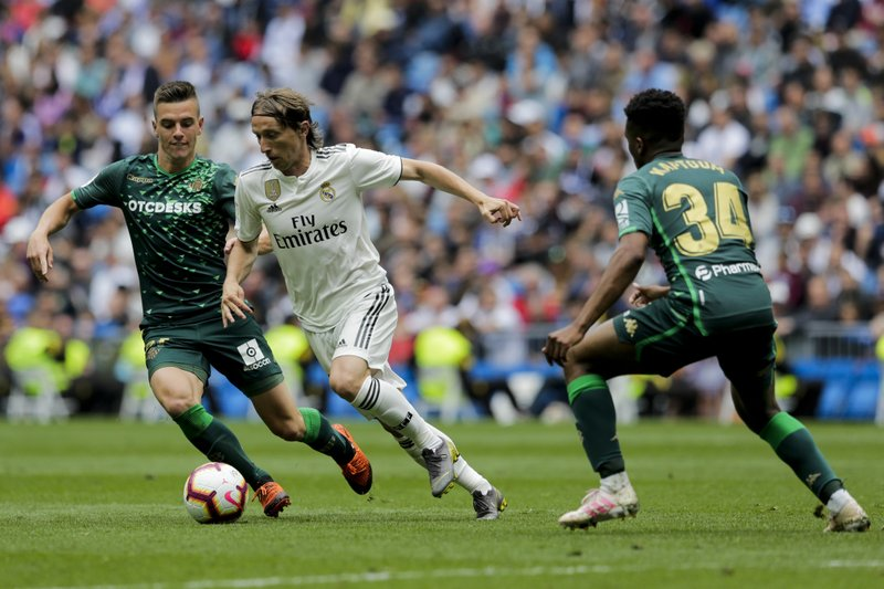 Real Madrid's Luka Modric, center, duels for the ball against Betis player Lo Celso, left and Betis player Kaptoum during a Spanish La Liga soccer match at the Santiago Bernabeu stadium in Madrid, Spain, Sunday, May 19, 2019. (AP Photo/Bernat Armangue)