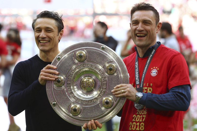 Bayern coach Nikon Kovac, left, and his brother Robert hold the trophy to celebrate Bayern's 7th straight Bundesliga title after the German Soccer Bundesliga match between FC Bayern Munich and Eintracht Frankfurt in Munich, Germany, Saturday, May 18, 2019. (AP Photo/Matthias Schrader)