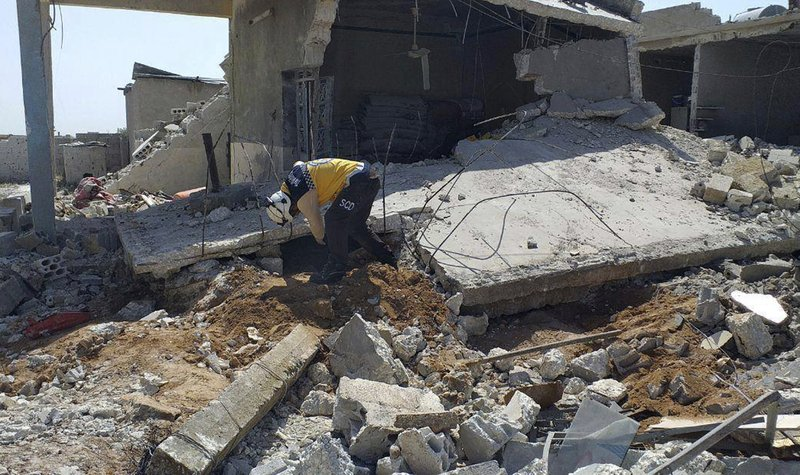 FILE - In this May 7, 2019 file photo provided by the Syrian Civil Defense group known as the White Helmets, shows a member of the White Helmets, searching for victims under the rubble of a house that was destroyed by a Syrian government forces airstrike, in the village of Ras el-Ain, in the northwestern province of Idlib, Syria. Russia said Sunday, May 19, 2019, that Syrian government forces have unilaterally ceased fire in the northern Idlib province, the last major rebel stronghold. Fighting erupted in Idlib last month, effectively shattering a cease-fire negotiated by Russia and Turkey that had been in place since September. (Syrian Civil Defense White Helmets via AP, File)