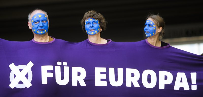 People, with faces painted like a European flag, arrive for a demonstration in Berlin, Germany, Sunday, May 19, 2019. People across Europe attend demonstrations under the slogan 'A Europe for All - Your Voice Against Nationalism'. The banner reads 'For Europe