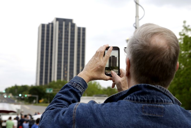 A man uses a phone to record Martin Tower, former world headquarters of Bethlehem Steel, before it implodes Sunday, May 19, 2019, in Bethlehem, Pa. Crowds gathered to watch the demolition of the area's tallest building, a 21-story monolith that opened at the height of Bethlehem Steel's power and profitability but had stood vacant for a dozen years after America's second-largest steelmaker went out of business. (AP Photo/Jacqueline Larma)