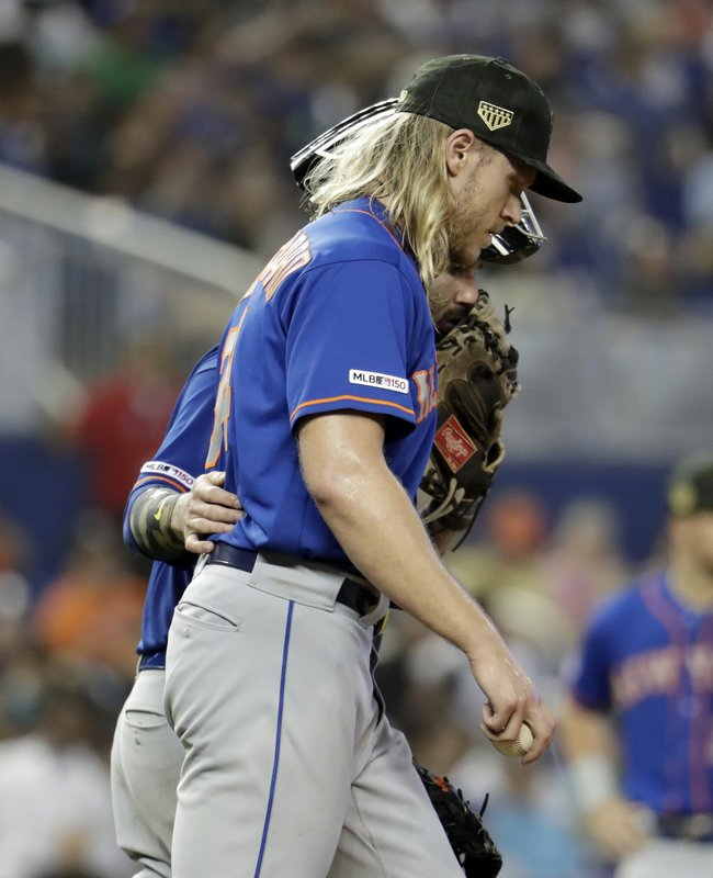 New York Mets starting pitcher Noah Syndergaard talks with catcher Tomas Nido, left, in the sixth inning of a baseball game, Sunday, May 19, 2019, in Miami. (AP Photo/Lynne Sladky)