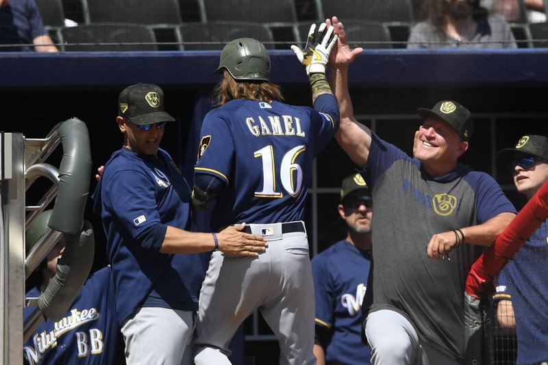 Milwaukee Brewers' Ben Gamel is congratulated as he enters the dugout after hitting the go-ahead home against the Atlanta Braves during the 10th inning of a baseball game Sunday May 19, 2019, in Atlanta. Milwaukee won 3-2. (AP Photo/John Amis)