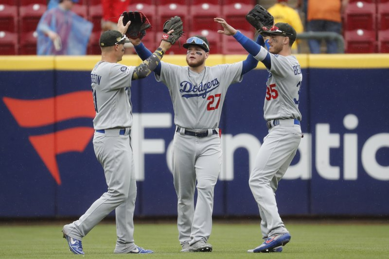 Los Angeles Dodgers center fielder Alex Verdugo (27) celebrates with first baseman Cody Bellinger (35) and left fielder Joc Pederson, left, after closing the ninth inning of a baseball game against the Cincinnati Reds, Sunday, May 19, 2019, in Cincinnati. (AP Photo/John Minchillo)