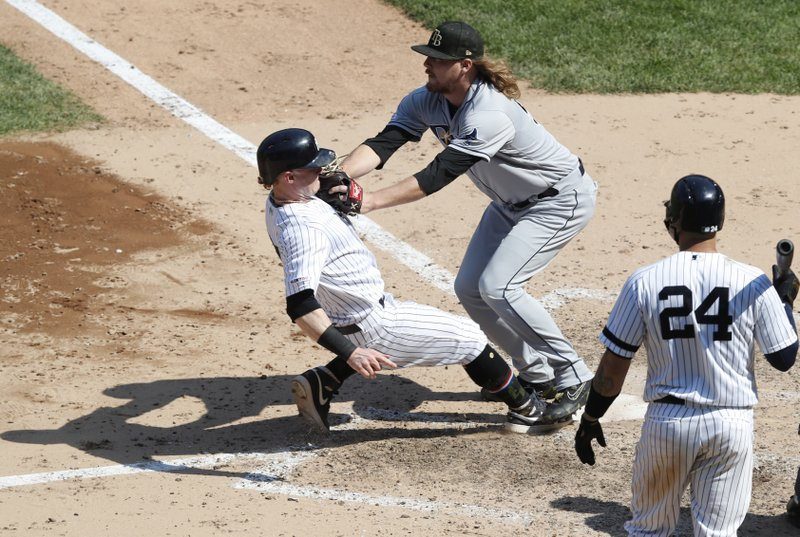 Tampa Bay Rays relief pitcher Ryne Stanek (55) tags New York Yankees Clint Frazier (77) out at the plate during the sixth inning of a baseball game, Sunday, May 19, 2019, in New York. New York Yankees batter Gary Sanchez (24) watches the play. (AP Photo/Kathy Willens)