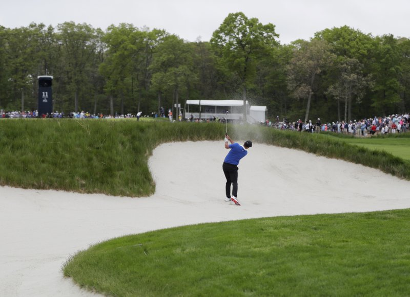 Brooks Koepka hits out of a bunker on the 11th hole during the final round of the PGA Championship golf tournament, Sunday, May 19, 2019, at Bethpage Black in Farmingdale, N.Y. (AP Photo/Julio Cortez)