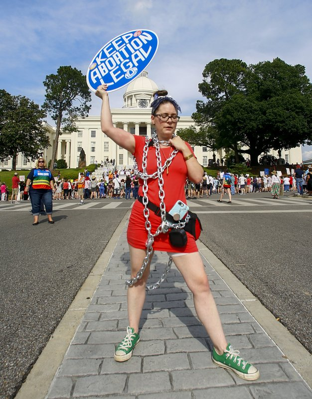 Kelly Thompson stands in front of the Alabama Capitol to protest a law passed last week making abortion a felony in nearly all cases with no exceptions for cases of rape or incest, Sunday, May 19, 2019, in Montgomery, Ala. (AP Photo/Butch Dill)