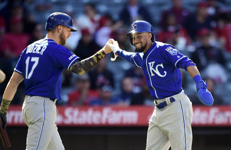 Kansas City Royals' Billy Hamilton, right, is congratulated by Hunter Dozier after scoring with the bases loaded when Alex Gordon was hit by a pitch during the ninth inning of a baseball game against the Los Angeles Angels Sunday, May 19, 2019, in Anaheim, Calif. (AP Photo/Mark J. Terrill)