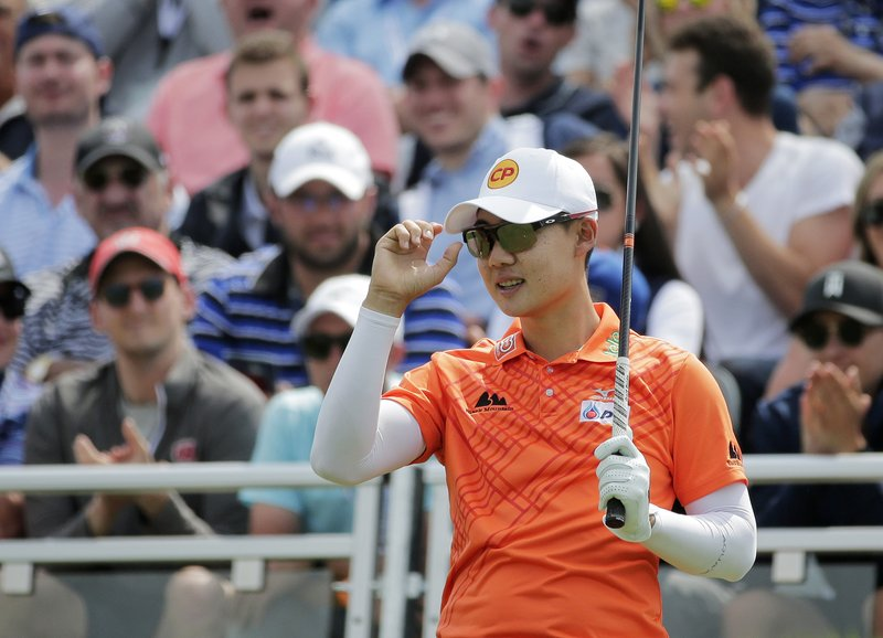 Jazz Janewattananond, of Thailand, acknowledges applause from spectators before driving off the first tee during the final round of the PGA Championship golf tournament, Sunday, May 19, 2019, at Bethpage Black in Farmingdale, N.Y. (AP Photo/Seth Wenig)