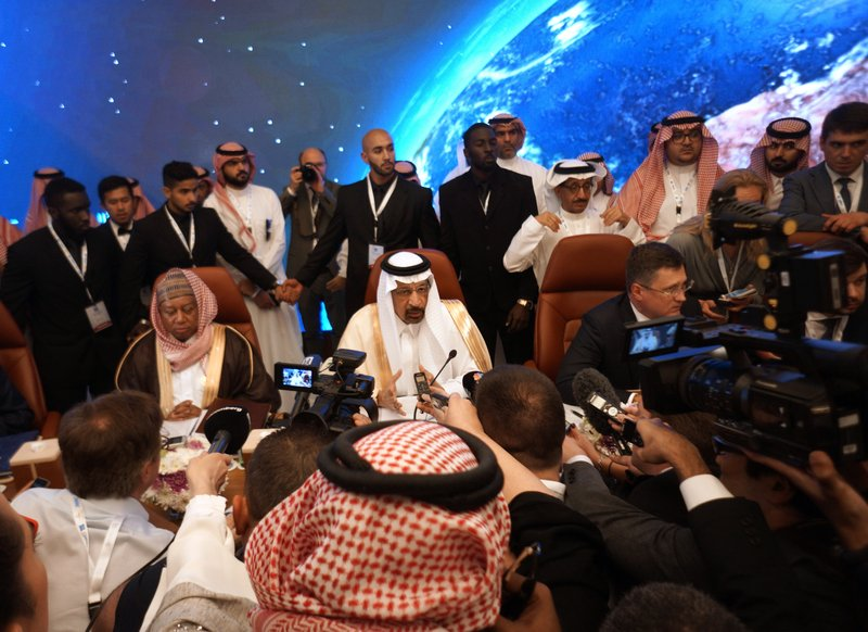 Russian Minister of Energy Alexander Novak, center right, Saudi Minister of Energy, Industry and Mineral Resources Khalid al-Falih, center, and OPEC Secretary General, Mohammed Sanusi Barkindo, center left, are surrounded by reporters during the opening of a meeting of energy ministers from OPEC and its allies to discuss prices and production cuts, in Jiddah, Saudi Arabia, Sunday, May 19, 2019. The meeting takes places as tensions flare in the Persian Gulf after the U.S. ordered bombers and an aircraft carrier to the region over an unexplained threat they perceive from Iran, which comes a year after the U.S. unilaterally pulled out of Tehran's nuclear deal with world powers and reimposed sanctions on Iranian oil. (AP Photo/Amr Nabil)
