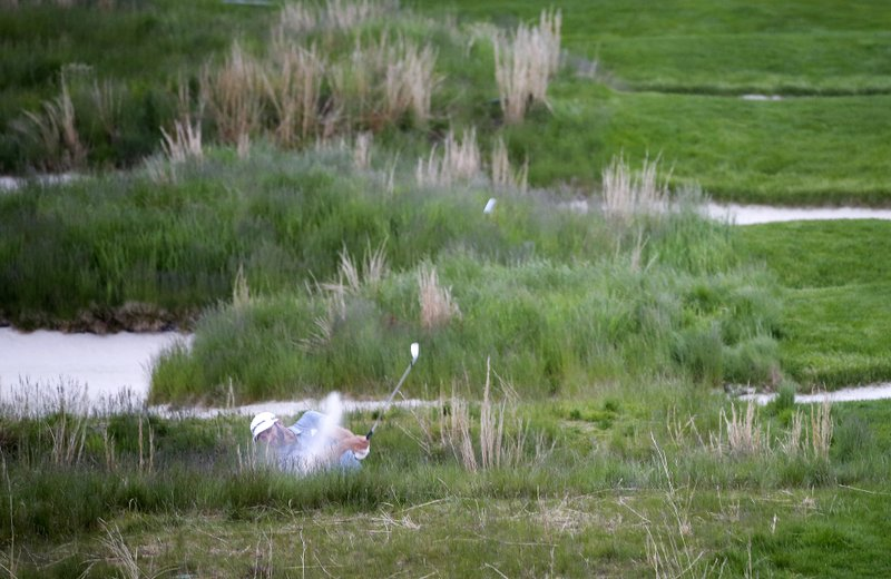 Dustin Johnson hits out of a bunker along the 18th fairway during the final round of the PGA Championship golf tournament, Sunday, May 19, 2019, at Bethpage Black in Farmingdale, N.Y. (AP Photo/Seth Wenig)
