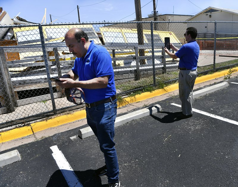 Hector Guerrero, the warning coordination meteorologist for the National Weather Service office in San Angelo, and fellow NWS forecaster Stephen Kearney, assess the damage to a portable building at Reagan Elementary School in Abilene, Texas, Sunday, May 19, 2019. The National Weather Service on Sunday reported a few tornadoes hit parts of San Angelo a day earlier. Another twister was reported Saturday in Ballinger. Another tornado struck Abilene. (Ronald W. Erdrich/The Abilene Reporter-News via AP)