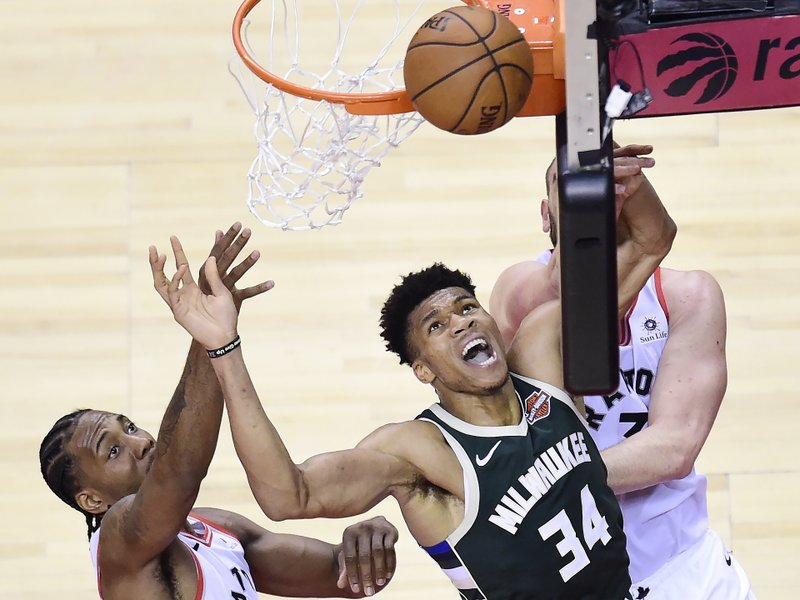 Milwaukee Bucks forward Giannis Antetokounmpo (34) misses a basket under pressure from Toronto Raptors forward Kawhi Leonard, left, and center Marc Gasol,  back right, during the second half of Game 3 of the NBA basketball playoffs Eastern Conference finals in Toronto, Sunday, May 19, 2019. (Frank Gunn/The Canadian Press via AP)