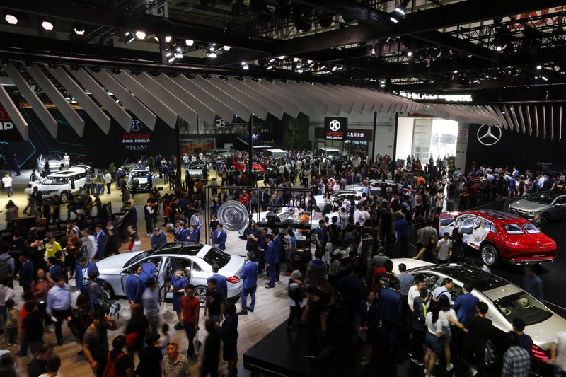FILE - In this April 29, 2018, file photo, visitors gather around car models displayed by Chinese and foreign automakers during the China Auto Show in Beijing. For four decades, Beijing has cajoled or pressured foreign companies to hand over technology. And its trading partners say if that didn't work, China stole what it wanted. (AP Photo/Andy Wong, File)
