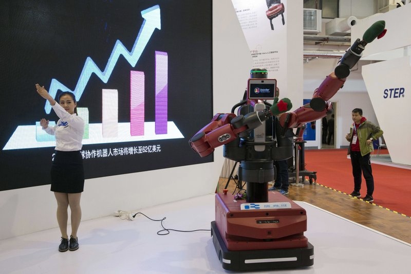 FILE - In this Oct. 21, 2016 photo, a Chinese woman demonstrates the ability of Baxter, an industrial robot from U.S. company Rethink Robotics, to follow her hand movements during the World Robot Conference in Beijing. For four decades, Beijing has cajoled or pressured foreign companies to hand over technology. And its trading partners say if that didn't work, China stole what it wanted. (AP Photo/Ng Han Guan, File)
