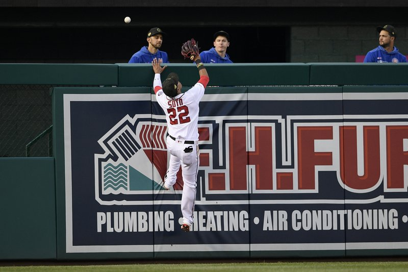 Washington Nationals left fielder Juan Soto (22) leaps for a ball that went for a home run by Chicago Cubs' Anthony Rizzo for a home run during the third inning of a baseball game, Sunday, May 19, 2019, in Washington. (AP Photo/Nick Wass)