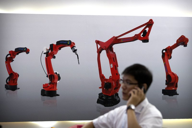 FILE - In this Aug. 15, 2018, file photo, a visitor talks on his smartphone in front of a display of manufacturing robots from a Chinese robot maker at the World Robot Conference in Beijing. In a report issued Monday, May 20, 2019, a business group says the number of foreign companies in China that feel compelled to hand over technology in exchange for market access has doubled since two years ago. (AP Photo/Mark Schiefelbein, File)