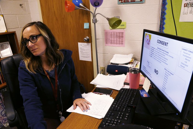 High school health teacher Cathy Booher listens to Wexford County prosecutor Jason Elmore talk to her freshman students about consent and criminal sexual conduct on Wednesday, April 17, 2019, in Cadillac, Mich. Booher says there's been progress in victims of sexual abuse and harassment coming forward, but she says too many students are still too reluctant to
