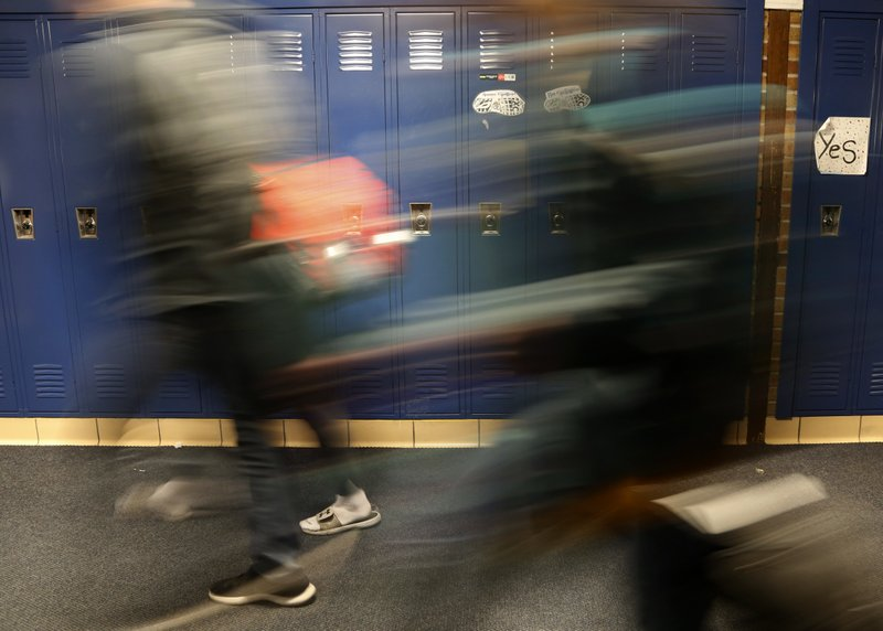 Students walk through a hallway at Cadillac High School in Cadillac, Mich., on Wednesday, April 17, 2019. The topic of consent for sexual activity - including the age when a student can legally say