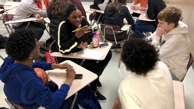 """Sophomore Ramaya Wright, 15, second from left, leads a group making a list of the characteristics of an abusive relationship, during a class at Central Catholic High School in Portland, Ore., on April 15, 2019. """"It, like, opened my eyes,"""" said Wright. """"I didn't know those are a lot of the signs of an abusive relationship."""" (AP Photo/Gillian Flaccus)"""