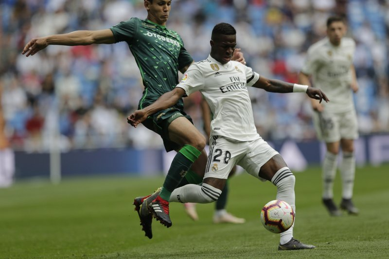 Real Madrid's Vinicius Junior, right, duels for the ball against Betis player Aissa Mandi during a Spanish La Liga soccer match at the Santiago Bernabeu stadium in Madrid, Spain, Sunday, May 19, 2019. (AP Photo/Bernat Armangue)