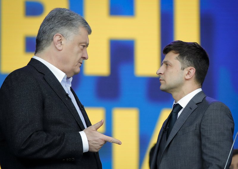 FILE - In this Friday, April 19, 2019 file photo, Ukrainian presidential candidate and popular comedian Volodymyr Zelenskiy listens to Ukrainian President Petro Poroshenko during their final electoral campaign debate at the Olympic stadium in Kiev, Ukraine. Volodymyr Zelenskiy, who takes the presidential oath on Monday May 20, 2019, comes into the post having never held political office; his popularity is rooted in playing the role of president on a television sit-com. (AP Photo/Vadim Ghirda, File)