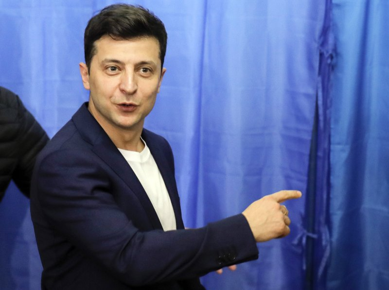 FILE - In this Sunday, April 21, 2019 file photo, Ukrainian comedian and presidential candidate Volodymyr Zelenskiy gestures at a polling station, during the second round of presidential elections in Kiev, Ukraine. Volodymyr Zelenskiy, who takes the presidential oath on Monday May 20, 2019, comes into the post having never held political office; his popularity is rooted in playing the role of president on a television sit-com. (AP Photo/Vadim Ghirda, File)