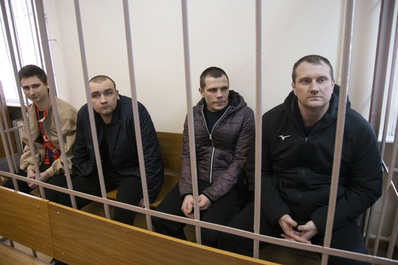 FILE - In this Wednesday, April 17, 2019 file photo, Ukrainian sailors sit in a cage in a courtroom in Moscow, Russia. Volodymyr Zelenskiy, who takes the presidential oath on Monday May 20, 2019, comes into the post having never held political office; his popularity is rooted in playing the role of president on a television sit-com.. (AP Photo/Alexander Zemlianichenko, File)
