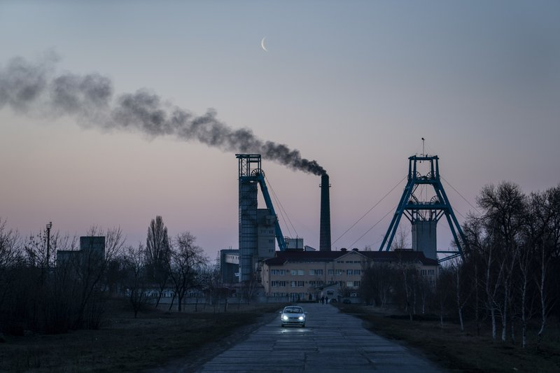 FILE - In this Monday, April 1, 2019 file photo, the Stepova coal mine just before dawn in Pershotravensk, Dnipropetrovsk region, eastern Ukraine. Volodymyr Zelenskiy, who takes the presidential oath on Monday May 20, 2019, comes into the post having never held political office; his popularity is rooted in playing the role of president on a television sit-com. (AP Photo/Evgeniy Maloletka, File)