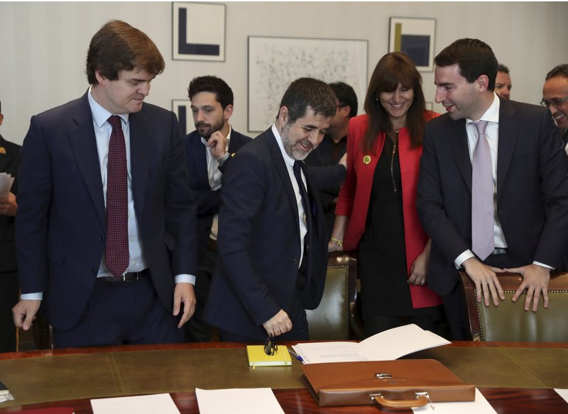 Jordi Sanchez, president of the Catalan National Assembly, center, prepares to sign some documents and collect his credentials inside the Spanish parliament in Madrid, Spain, Monday May 20, 2019. The five separatist leaders on trial for Catalonia's 2017 secession attempt who were elected to the Spanish Parliament in April 28 elections have been escorted by police to pick up their official parliament credentials. The Supreme Court is allowing the five politicians to get their credentials on Monday and attend the opening session of the new Parliament on Tuesday. (J.J. Guillen/Pool Photo via AP)