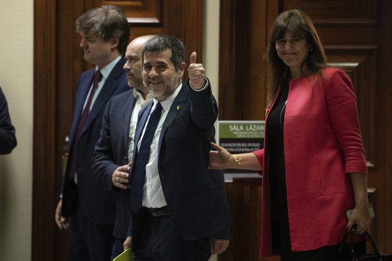 Catalan politician Jordi Sanchez gestures a thumbs up to the media after collecting his credential at the Spanish parliament in Madrid, Spain, Monday, May 20, 2019. Five separatist leaders on trial for Catalonia's 2017 secession attempt who were elected to the Spanish Parliament in April 28 elections have been escorted by police to pick up their official credentials. The five, along with other defendants, are being held in pre-trial jail. They face several years in prison if found guilty of rebellion. (AP Photo/Bernat Armangue)