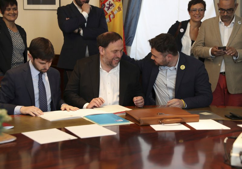 The leader of the Catalonian ERC party Oriol Junqueras, center, speaks with the ERC spokesperson for the parliament Gabriel Rufian, right, at the Spanish parliament in Madrid, Spain, Monday May 20, 2019. The five separatist leaders on trial for Catalonia's 2017 secession attempt who were elected to the Spanish Parliament in April 28 elections have been escorted by police to pick up their official parliament credentials. The Supreme Court is allowing the five politicians to get their credentials on Monday and attend the opening session of the new Parliament on Tuesday. (J.J. Guillen/Pool Photo via AP)
