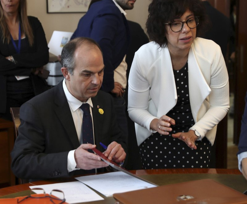 Catalan Councillor Jordi Turull, left, signs documents inside the Spanish parliament in Madrid, Spain, Monday May 20, 2019. The five separatist leaders on trial for Catalonia's 2017 secession attempt who were elected to the Spanish Parliament in April 28 elections have been escorted by police to pick up their official parliament credentials. The Supreme Court is allowing the five politicians to get their credentials on Monday and attend the opening session of the new Parliament on Tuesday.(J.J. Guillen/Pool Photo via AP)