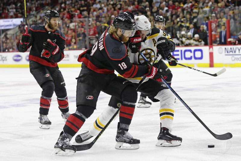 Carolina Hurricanes' Dougie Hamilton (19) and Boston Bruins' David Backes (42) chase the puck during the first period in Game 4 of the NHL hockey Stanley Cup Eastern Conference final series in Raleigh, N.C., Thursday, May 16, 2019. (AP Photo/Gerry Broome)