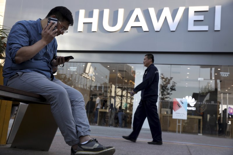 A man uses two smartphones at once outside a Huawei store in Beijing Monday, May 20, 2019. Google is assuring users of Huawei smartphones the American company's services still will work on them following U.S. government restrictions on doing business with the Chinese tech giant. (AP Photo/Ng Han Guan)