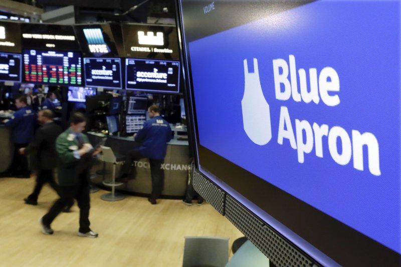 FILE - In this Thursday, Oct. 19, 2017, file photo, the logo for Blue Apron appears on a screen above the trading floor of the New York Stock Exchange. Meal kit companies face an ultimatum: Adapt or die. The struggle has intensified for Blue Apron, which announced that it could be delisted from the New York Stock Exchange because its closing share price has been lower than $1 since early May 2019. (AP Photo/Richard Drew, File)