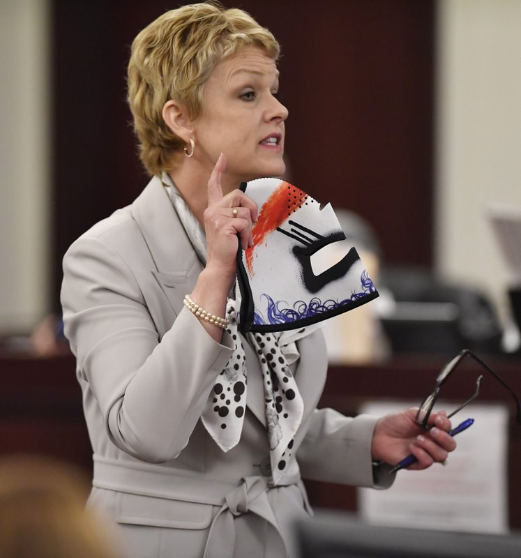 Jennifer Thompson, defense attorney for Emanuel Kidega Samson, holds a mask worn by Samson as she delivers her opening statement during the first day of Samson's trial Monday, May 20, 2019, in Nashville, Tenn. Samson is accused of fatally shooting a woman and wounding seven people at a Nashville church in 2017. Prosecutors have said they're seeking life without parole for Samson. (George Walker IV/The Tennessean via AP, Pool)