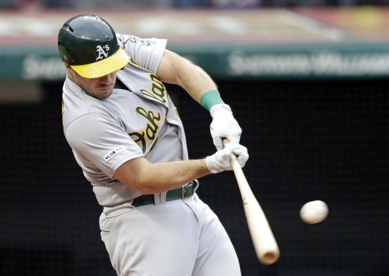 Oakland Athletics' Josh Phegley hits an RBI-single off Cleveland Indians starting pitcher Carlos Carrasco in the fourth inning of a baseball game, Monday, May 20, 2019, in Cleveland. Robbie Grossman scored on the play. (AP Photo/Tony Dejak)