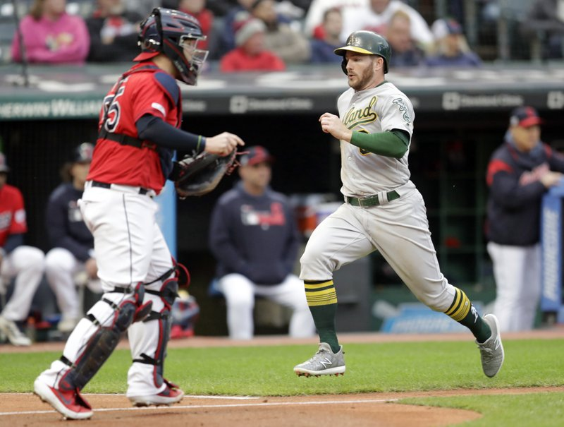 Oakland Athletics' Robbie Grossman, right, scores on Josh Phegley's single in the fourth inning of a baseball game against the Cleveland Indians, Monday, May 20, 2019, in Cleveland. Indians catcher Roberto Perez, left, looks on. (AP Photo/Tony Dejak)