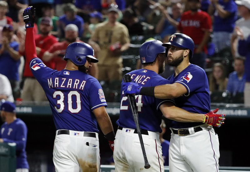 Texas Rangers' Nomar Mazara, Hunter Pence and Joey Gallo, celebrate a two-run home run by Pence that also scored Mazara in the seventh inning of a baseball game against the Seattle Mariners in Arlington, Texas, Monday, May 20, 2019. (AP Photo/Tony Gutierrez)