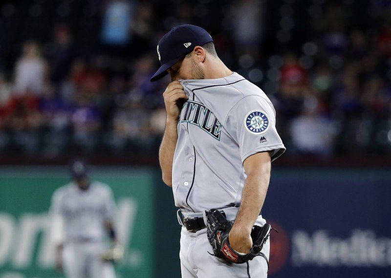 Seattle Mariners' Ryan Garton wipes his face as he stands on the mound after giving up a two-run home run to Texas Rangers' Hunter Pence in the seventh inning of a baseball game in Arlington, Texas, Monday, May 20, 2019. (AP Photo/Tony Gutierrez)
