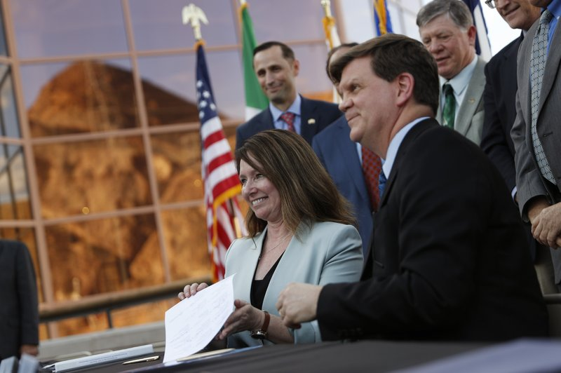 Bureau of Reclamation chief Brenda Burman, left, and Interior Department official Tim Petty, celebrate with representatives from seven states during a ceremony for a Colorado River drought contingency plan, Monday, May 20, 2019, in Boulder City, Nev. (AP Photo/John Locher)