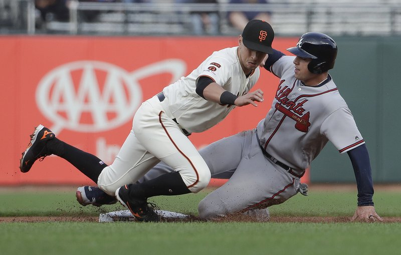 San Francisco Giants second baseman Joe Panik, left, tags out Atlanta Braves' Austin Riley trying to steal second base during the second inning of a baseball game in San Francisco, Monday, May 20, 2019. (AP Photo/Jeff Chiu)