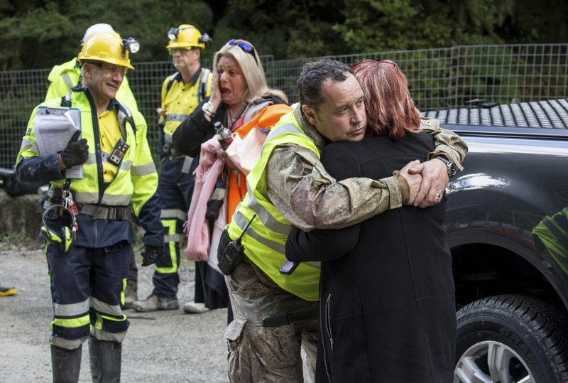 In this image released by the Pike River Recovery Agency, Dinghy Pattinson, left, stands with, Sonya Rockhouse, as Karl Maddaford embraces Anna Osborne before the re-entry the Pike River Mine, near Greymouth on the West Coast of New Zealand, Tuesday, May 21, 2019. Crews in New Zealand on Tuesday reentered an underground coal mine where a methane explosion killed 29 workers more than eight years ago, raising hopes among family members that they might find bodies and new evidence that leads to criminal charges. (Neil Silverwood/Pike River Recovery Agency via AP)