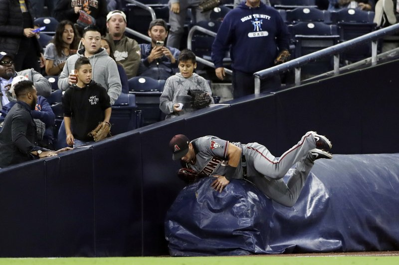 Arizona Diamondbacks left fielder David Peralta runs into a rolled mat after making a catch for the out on San Diego Padres' Eric Hosmer during the fourth inning of a baseball game Monday, May 20, 2019, in San Diego. (AP Photo/Gregory Bull)