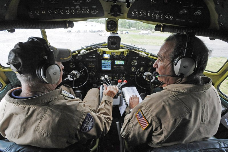 In this April 9, 2019, photo, Pilot Tom Travis, left, and Phil Bonasera sit at the controls of the World War II troop carrier That's All, Brother in Birmingham, Ala. Found in a Wisconsin aviation boneyard and restored, the C-47 named will drop paratrooper re-enactors over the French coast in June 2019, marking the 75th anniversary of D-Day. (AP Photo/Jay Reeves)