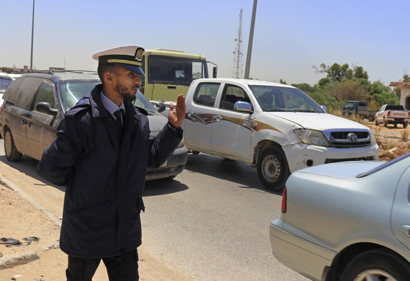 In this May 2, 2019 photo, a police officer waves vehicles through a checkpoint during rush hour in Benghazi, Libya. After years of assassinations, bombings and militia firefights, Libya's eastern city of Benghazi finally feels safe again -- but security has come at a staggering cost. The city center lies in ruins, thousands of people remain displaced, and forces loyal to Khalifa Hifter, who now controls eastern Libya, have cracked down on dissent. (AP Photo/Rami Musa)